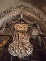 Escudo de la familia Schwarzenberg; atrás una torre de huesos.